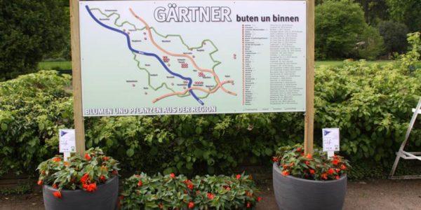 Spezielles Standschild von Grünewald-Werbung mit Blumen als Fuß